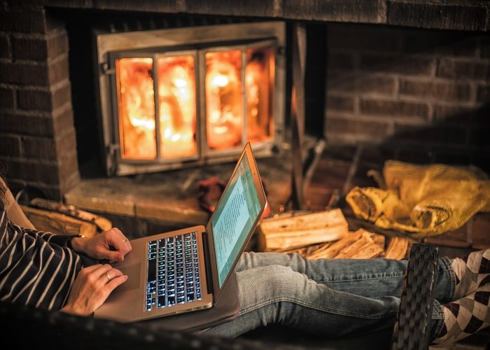 Woman working with a laptop at the warmth of the fireplace